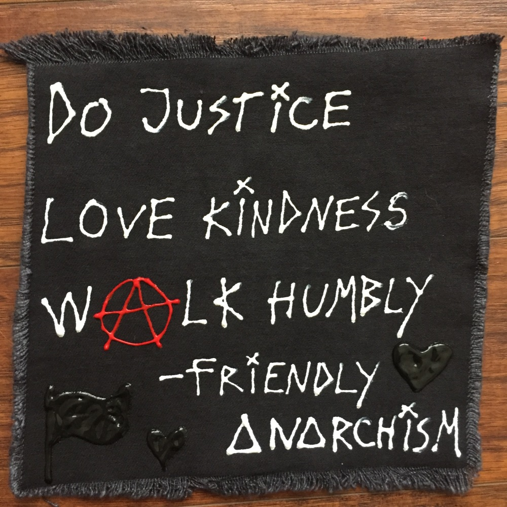 "Square black canvas patch. Handwritten in white puffy paint ""Do Justice, Love Kindness, Walk Humbly – Friendly Anarchism"""